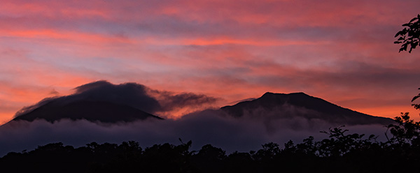 Sunrise Tenorio 1 and Tenorio 2 to the left under the cloud (view from our room) © 2015 Bob Harvey