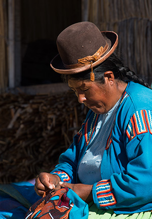 Resident of Uros, working on embroidery. © 2016 Bob Harvey